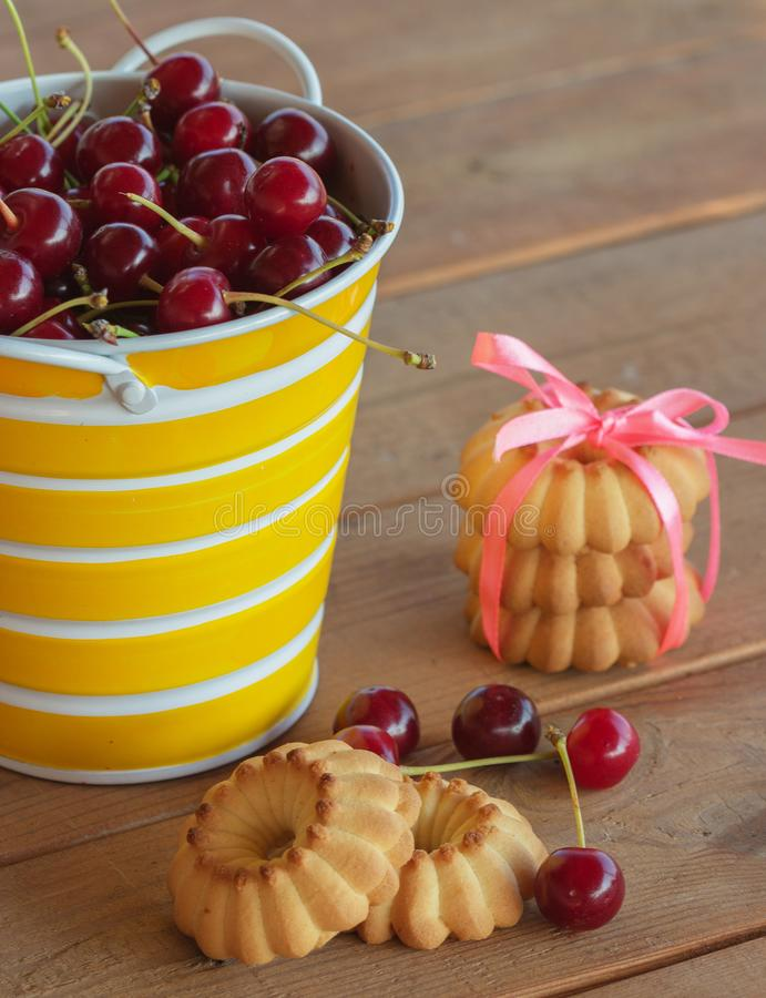 Sweet cherries in a striped yellow-white pail. On a wooden table royalty free stock image