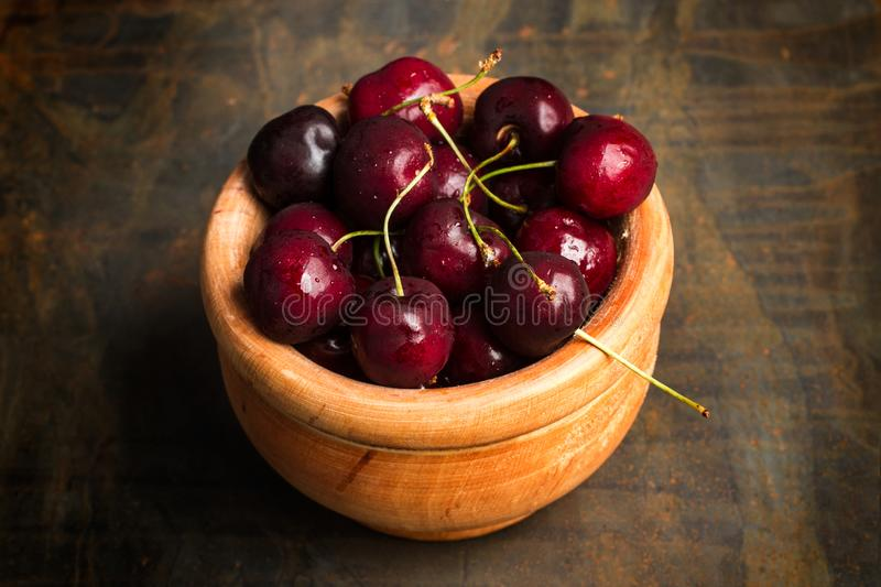 Sweet cherries in a wooden bowl stock images