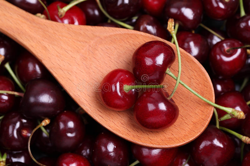 Sweet cherries in a wooden spoon royalty free stock images