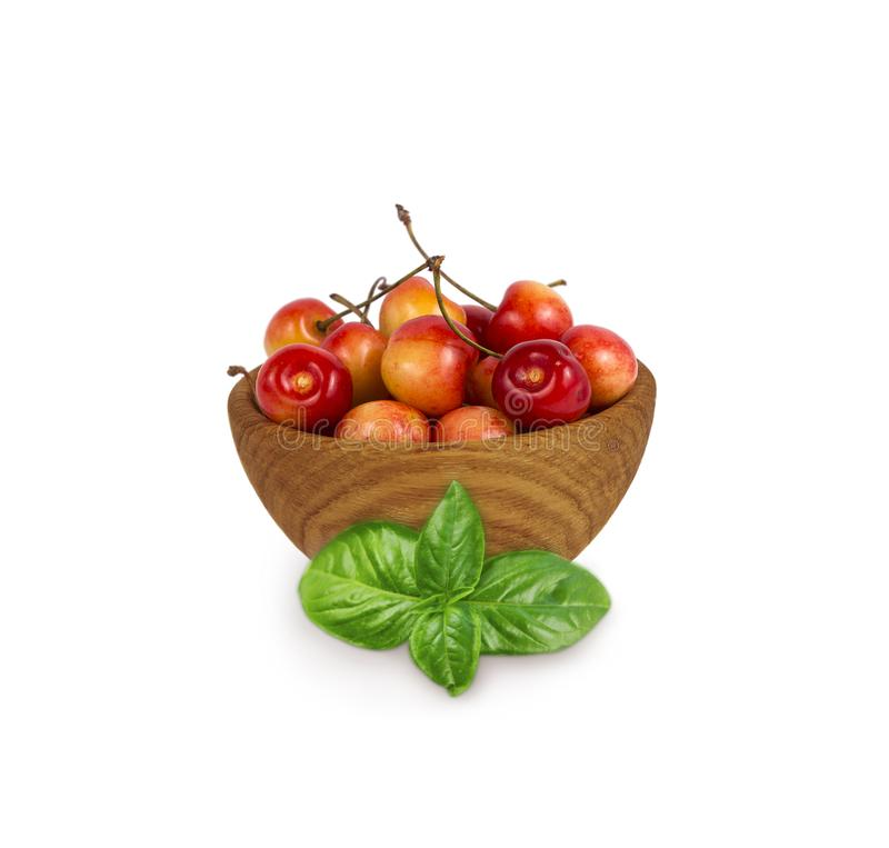Sweet cherry berries in with basil wooden bowl isolated on white royalty free stock image