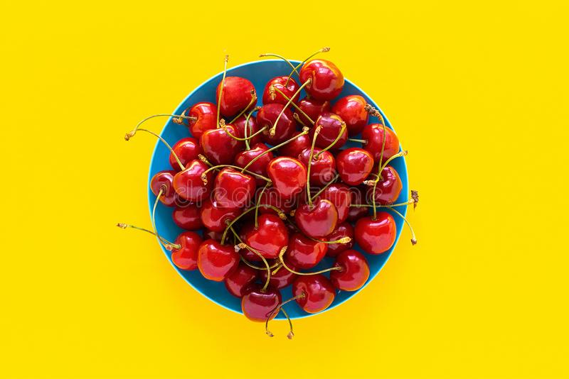 Sweet cherry on plate, yellow background royalty free stock photography