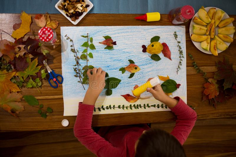 Sweet child, boy, applying leaves using glue. While doing arts and crafts in school, autumn time stock photos