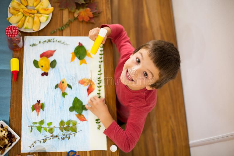Sweet child, boy, applying leaves using glue. While doing arts and crafts in school, autumn time royalty free stock photos