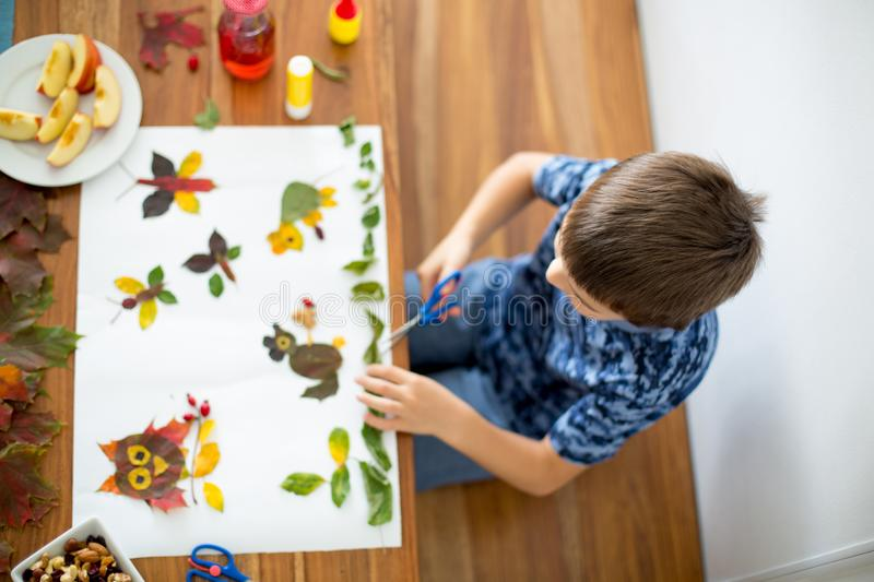 Sweet child, boy, applying leaves using glue. While doing arts and crafts in school, autumntime stock photography