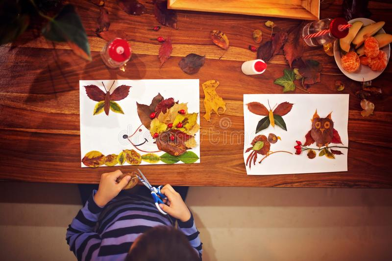 Sweet child, boy, applying leaves using glue while doing arts an. D crafts in school, autumntime royalty free stock photo