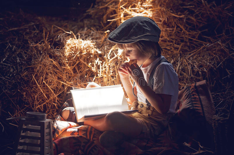 Sweet child, boy, reading a book on the attic on a house, sitting on a hay of straw royalty free stock photos