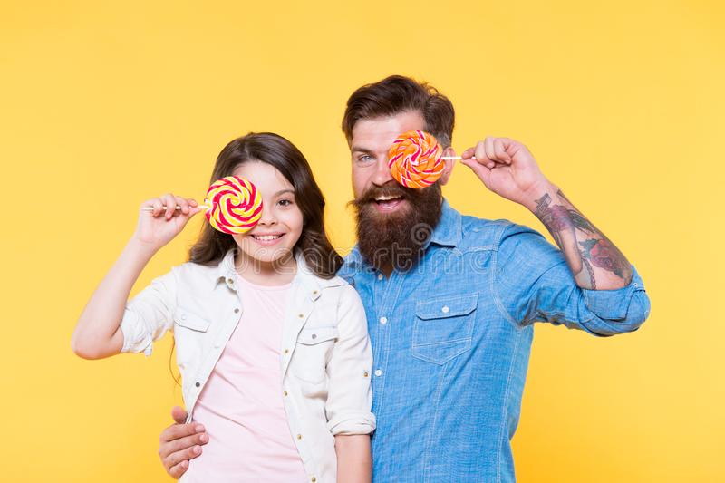 Sweet childhood. Girl child and dad hold colorful lollipops. Sweet dessert. Bearded hipster good daddy for adorable stock images
