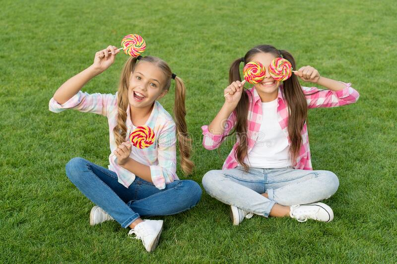 Sweet childhood. Happy children hold candy sit green grass. Candy shop. Lollipop treats. Candy synonym for happiness. Sugar and calories. Joyful cheerful royalty free stock photo