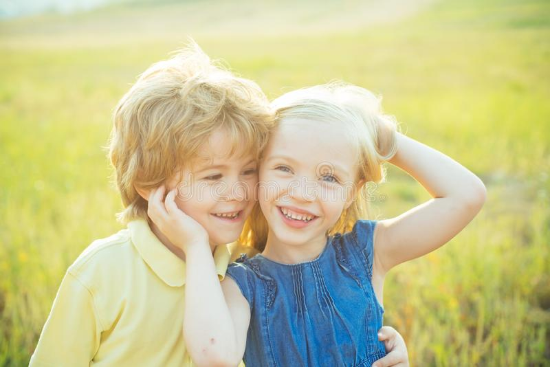 Sweet childhood. Happy Kid on summer field. Childcare. Happy children girl and boy hug on meadow in summer in nature. Valentines day cupid child. Childhood stock photography