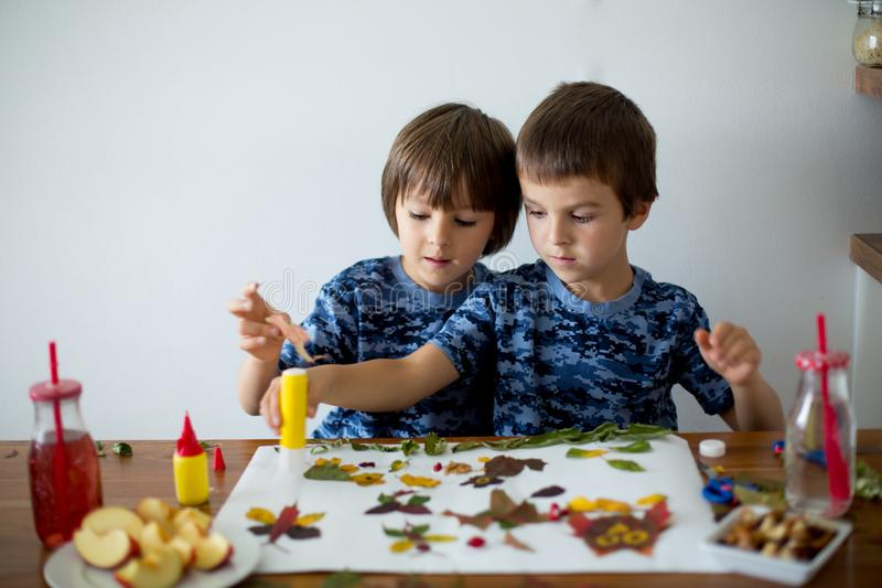Sweet children, boys, applying leaves using glue. While doing arts and crafts in school, autumn time stock images