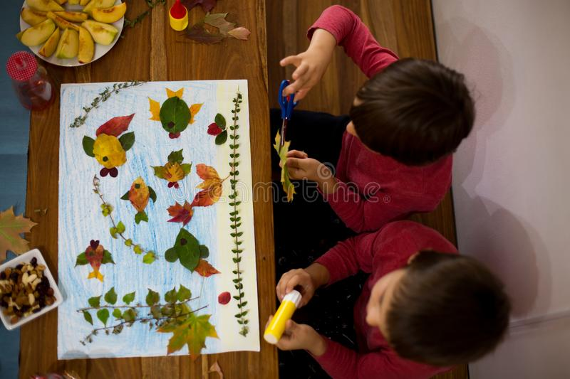 Sweet children, boys, applying leaves using glue. While doing arts and crafts in school, autumn time royalty free stock photography