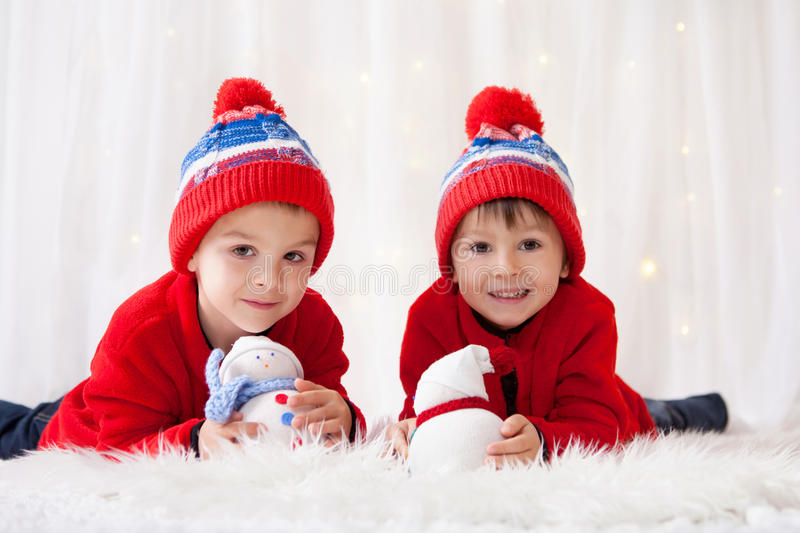 Sweet children, brother boys, playing with handmade snowmen at h royalty free stock photography