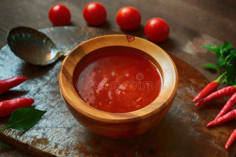 Sweet chili sauce. Tomatoes, silver spoon and hot red chili pepper on the brown wooden retro plate stock photos