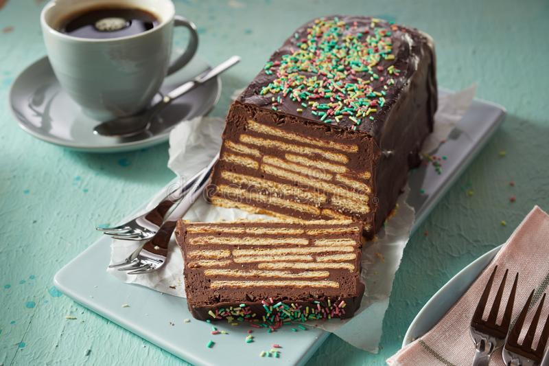 Sweet chocolate cake with biscuits and topping. Served on blue ceramic tray and with a cup of black coffee stock images