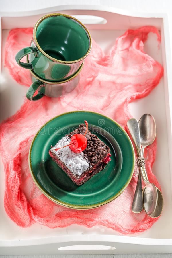 Sweet chocolate cake with cherry and crumble on green porcelain. On old white table royalty free stock image