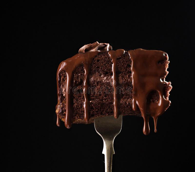 Sweet chocolate cake on fork on black macro background royalty free stock photo
