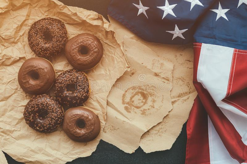 Sweet chocolate donuts and american flag, top view royalty free stock image