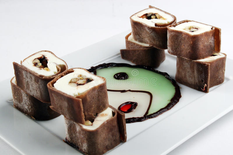 Sweet chocolate roll dessert. Sweet chocolate roll with fruits and philadelphia cheese in mint sauce royalty free stock images