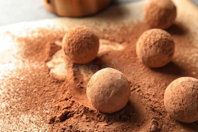 Sweet chocolate truffles powdered with cacao on parchment paper stock image