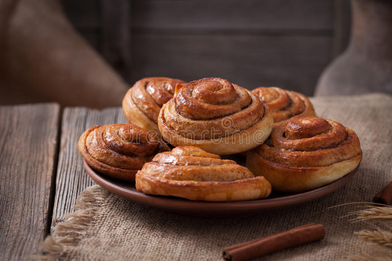 Sweet cinnamon bun rolls christmas homemade. Delicious sweet iced dessert on vintage woonde table. Traditional swedish kanelbullar baked pastry royalty free stock photography