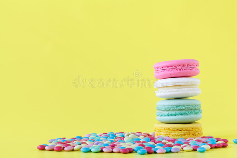 Sweet and colorful French macarons on yellow background stock images