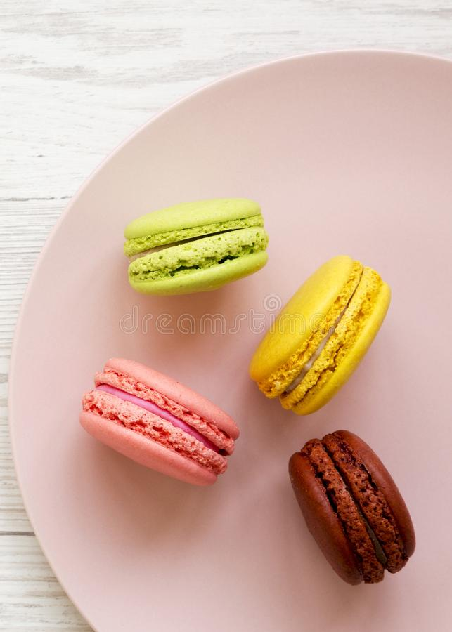 Sweet and colorful macarons on a pink plate over white wooden surface, top view. Close-up. Flat lay, overhead, from above.  stock image