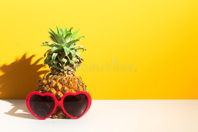 Sweet colorful pineapple tropical fruit with fashion red heart sunglasses, hot summer season vacation holiday, yellow. Pineapple tropical fruit with fashion red stock photo