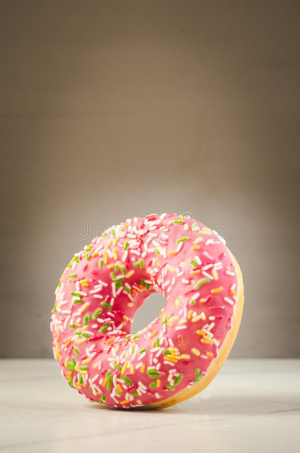 Sweet and colourful doughnut/Sweet and colourful doughnut with falling on a white table stock images