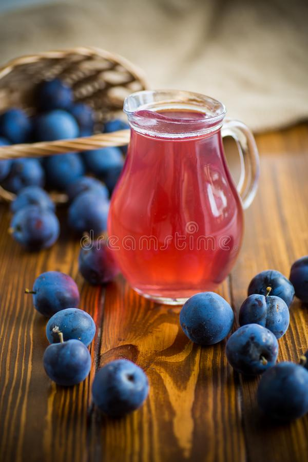 Sweet compote of autumn blue plums in a glass decanter. On a wooden table stock photo