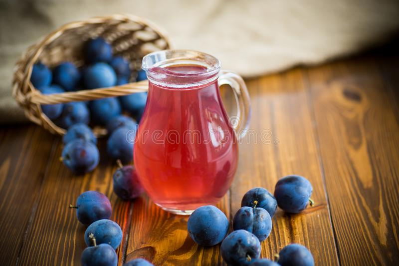 Sweet compote of autumn blue plums in a glass decanter. On a wooden table stock photos