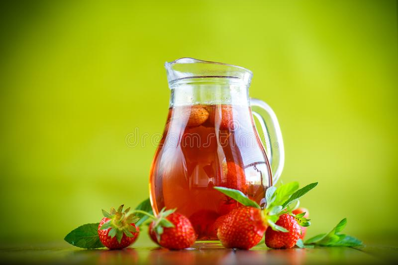 Sweet compote of ripe red strawberries in a glass decanter. On a table stock image