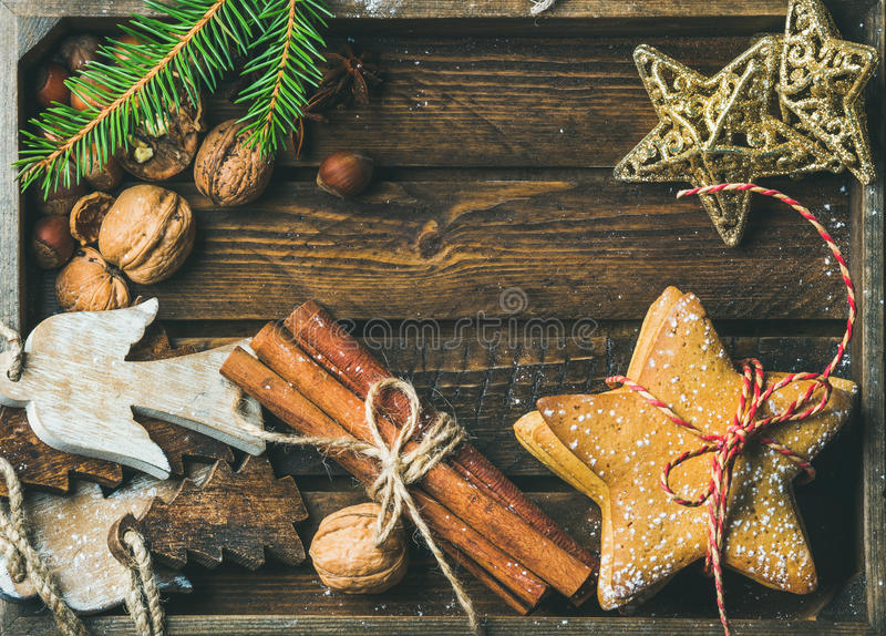 Sweet cookies, wooden angels, decorative golden stars, nuts, cinnamon sticks royalty free stock photography