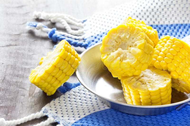 Download Sweet Corn Cob Pieces On Wooden Table With Navy Blue Kitchen Towel  Stock Photo