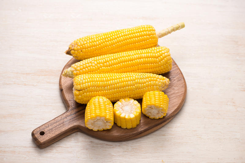 Sweet corn on cobs on cutting board on wooden table. stock photo