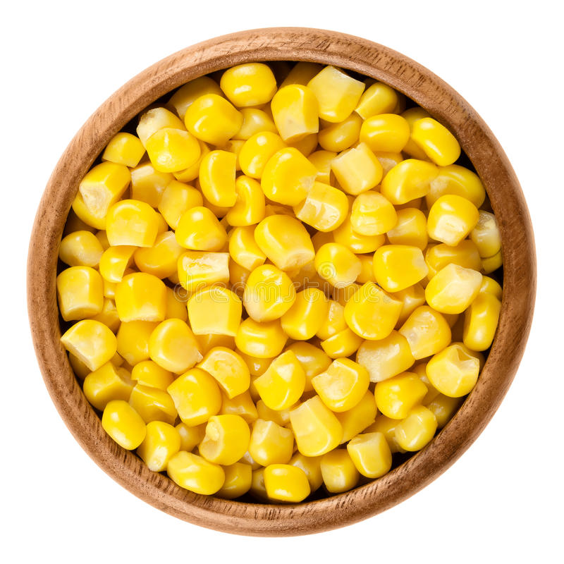 Sweet corn kernels in wooden bowl over white. Cooked canned yellow vegetable maize, Zea mays, also called sugar or pole corn, a vegetarian staple food stock photography