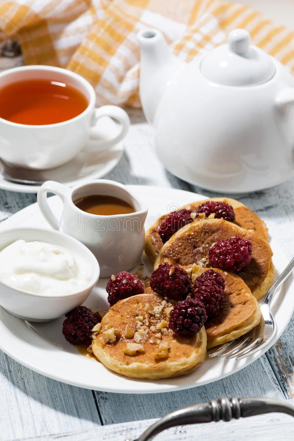Sweet corn pancakes with berries and caramel sauce on white table. Vertical royalty free stock image
