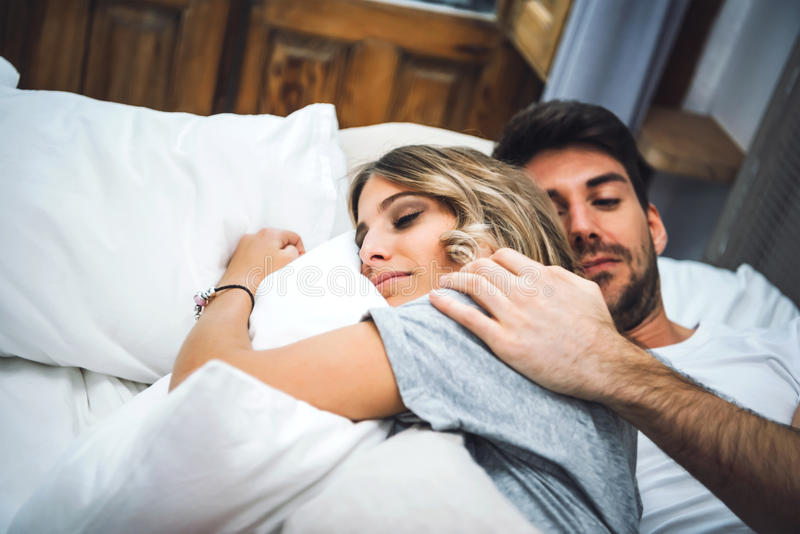 Sweet couple embracing in bed stock photo