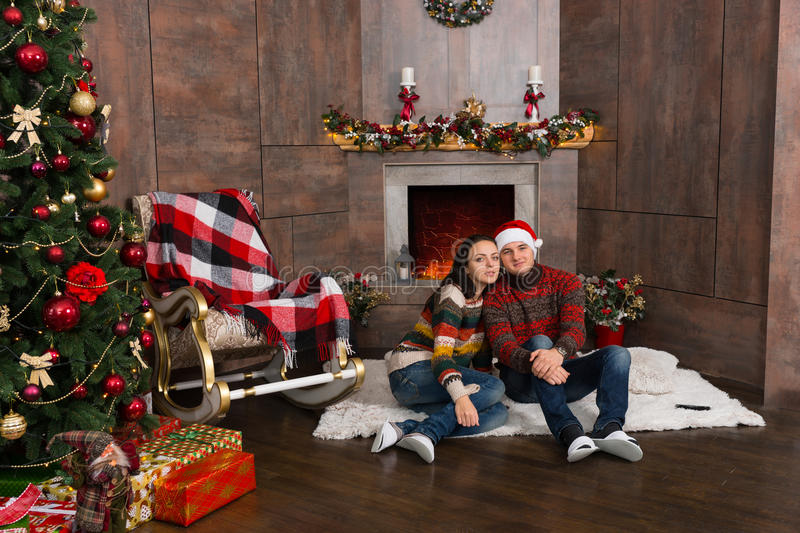 Sweet couple sitting on a rug in front of the decorated fireplace and near Christmas tree with presents stock photo