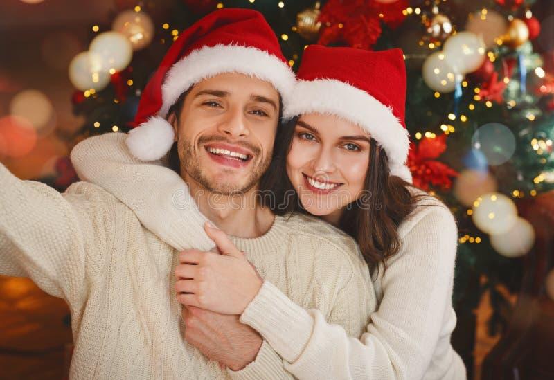 Sweet couple taking selfie on Christmas eve royalty free stock image