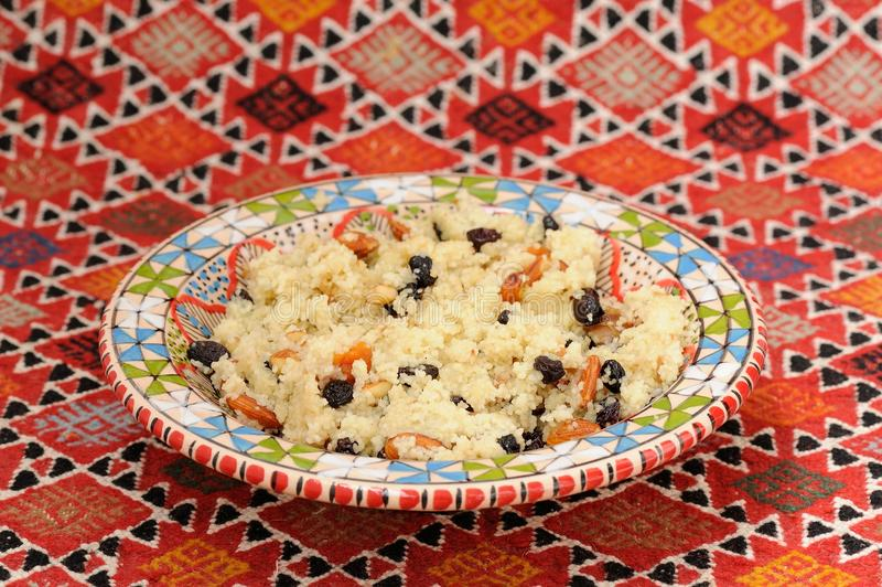 Sweet couscous with almond and dried fruits on red handmade carp royalty free stock images