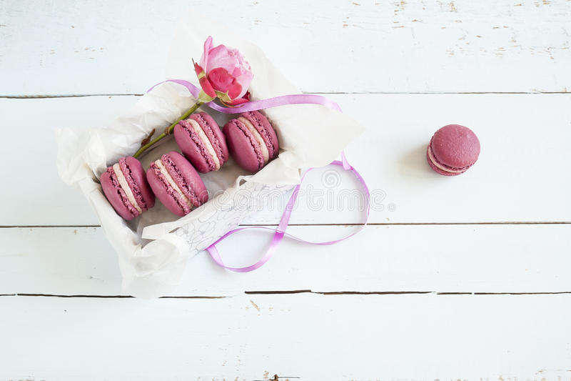 Sweet crimson french macaroons and rose with box on light dyed wooden background. Holidays background stock images