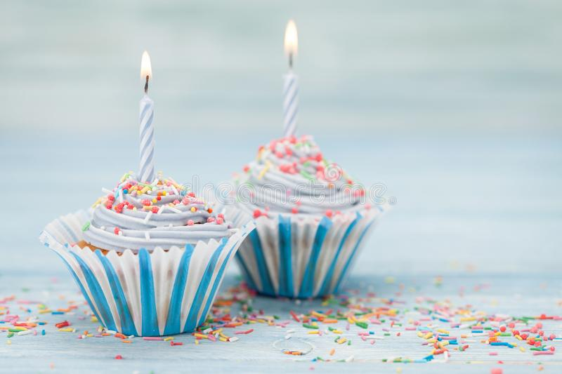 Sweet cupcakes with candles stock photography