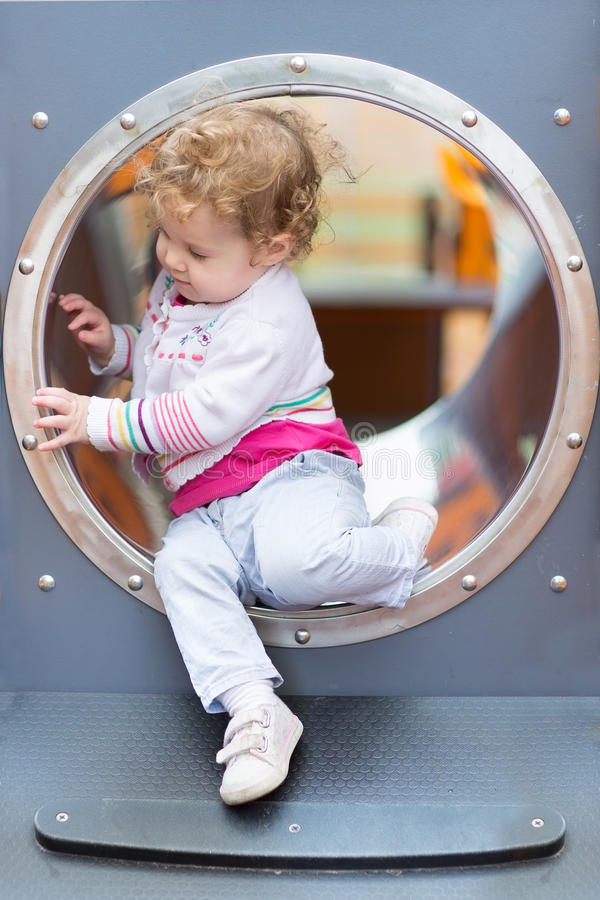 Sweet curly baby girl sliding on a playground stock photo