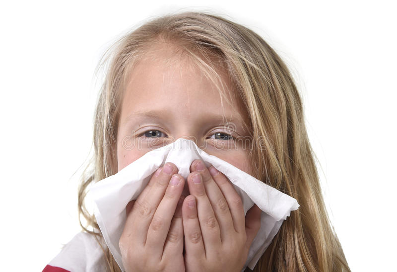 Sweet and cute blond hair little girl blowing her nose with paper tissue having a cold feeling sick royalty free stock photos