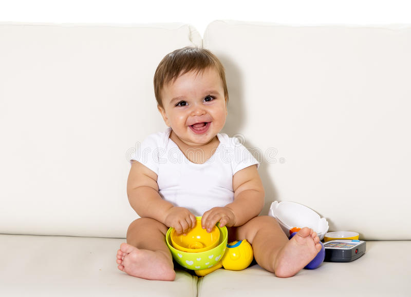 Sweet cute little baby sitting on couch alone at home playing with toys happy and relaxed having fun stock images