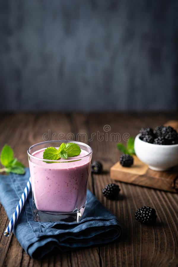 Sweet dairy drink, blackberry milkshake in a glass with copy space stock photo