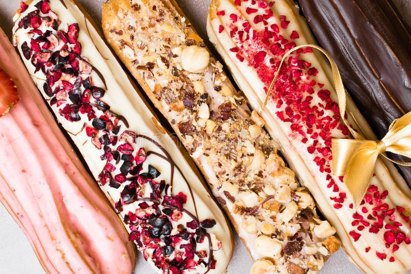 Sweet and colorful french eclairs with berrys, chocolate, nuts, decorated with bow. Group of french dessert. Eclair background. De royalty free stock photography