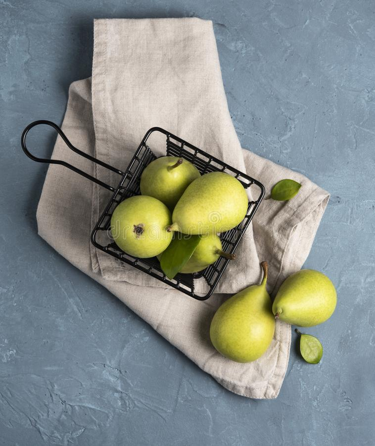 Sweet delicious green  pears inside  black basket on the blue table fruit royalty free stock photos