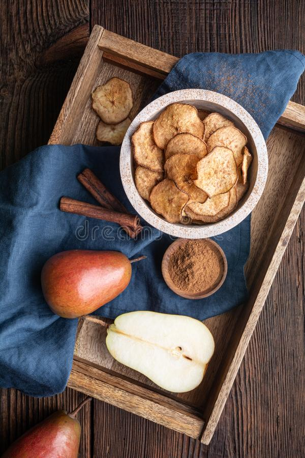 Sweet delicious snack, homemade oven dried crispy pear chips sprinkled with cinnamon royalty free stock image