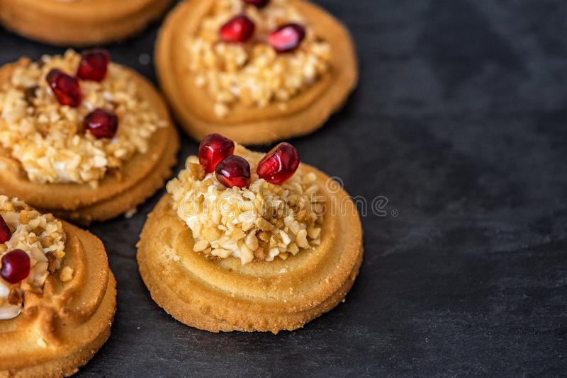Sweet dessert. Cream cookies sprinkled with nuts and garnished with pomegranate seeds. Close Up stock photos